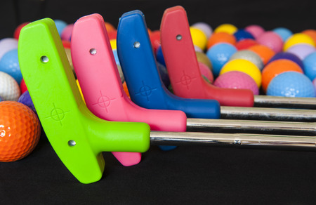 Four colorful mini golf putters with and assortment of balls Stock Photo