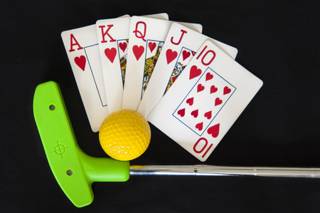 Mini golf club and ball with a royal flush poker hand Stock Photo