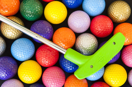 miniatures: Green mini golf putter with balls of assorted colors