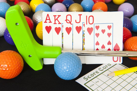 Royal flush poker hand with mini golf putter, balls and score card Stock Photo