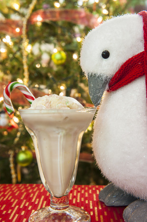 Christmas penguin looks at a dish of candy cane ice cream in front of the Christmas tree