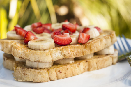 Tropical breakfast outdoor of French toast with bananas and strawberries