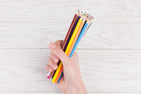 Colour pencils in hand on white wooden background photo
