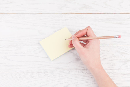 Woman hand writing on reminder notes with wood pencil on wooden table