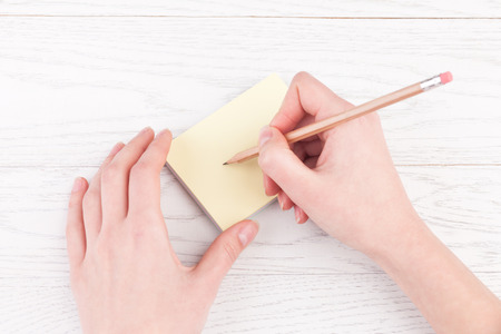 stiker: Woman hands writing on reminder notes with wood pencil on wooden table