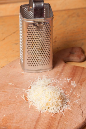 grated parmesan cheese: Italian grated parmesan cheese on wooden table Stock Photo