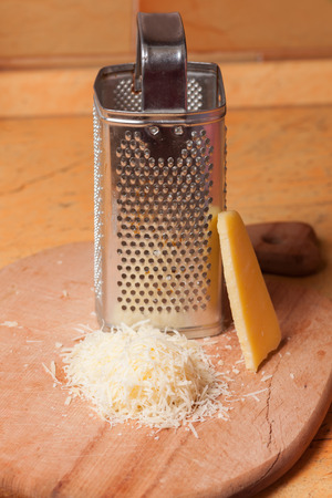 parmesan cheese: Italian grated parmesan cheese on wooden table Stock Photo