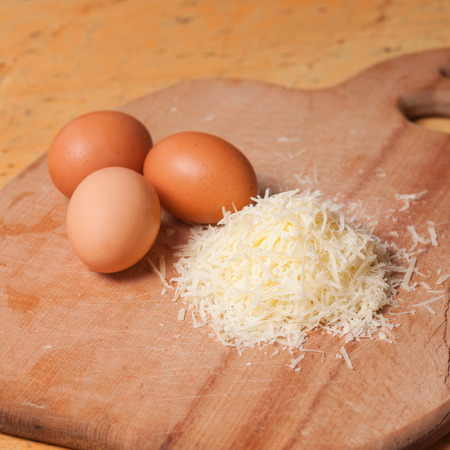 parmesan cheese: Italian grated parmesan cheese and eggs on wooden table Stock Photo