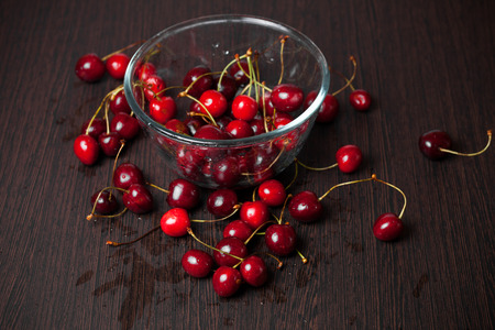 Fresh cherries in a glass bowl on wood table photo