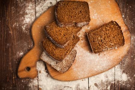 Sliced rye bread on cutting board closeup on wood table photo