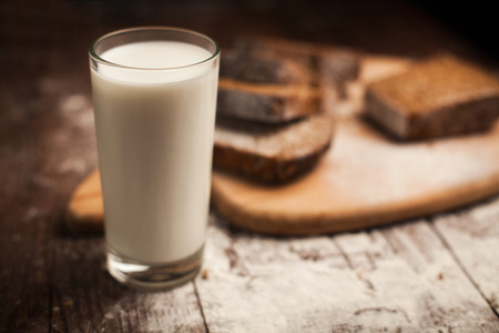 Milk and bread on wood table. still life photo
