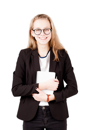 businesswoman suit: Girl smile into the camera and hold notepad  isolated on white