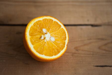 Half of orange on wooden ow background with copy space for your text 版權商用圖片