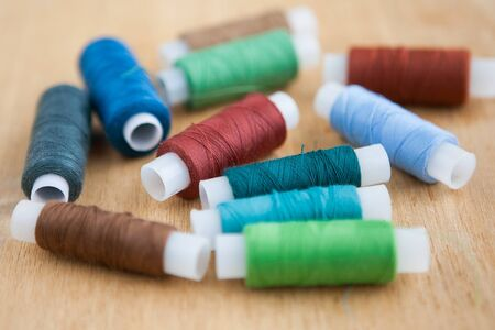 Sewing threads of different colors on wooden background