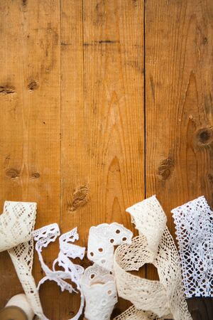 White laces on wooden background with the space for your text