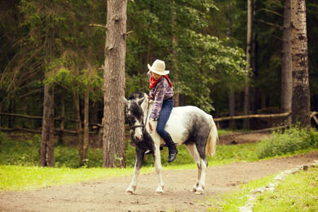 Young girl on the horse in the forest. Equestrian girl. Hatted cowgirl.