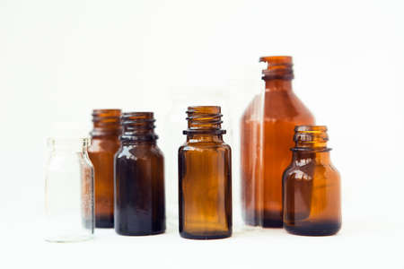 Dark brown phials on white background. Small empty bottles Banque d'images