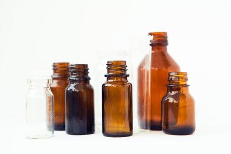 Dark brown phials on white background. Small empty bottles Stock fotó
