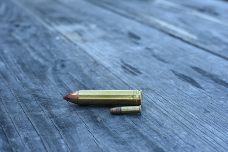 Red tip 450 Caliber ammunition and 22 Caliber side way on wooden background