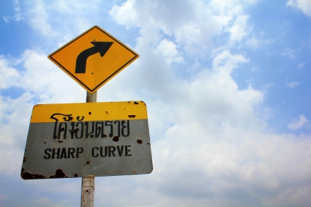 sharp curve: The sharp curve sign in front of the blue sky background