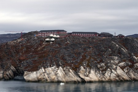 Greenland fiord fjord houses hotel rock near ocean tower crane