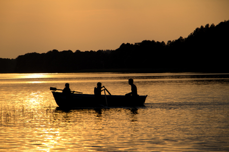 rowing wooden boat on lake in late evening with two girls and father people silhouettes