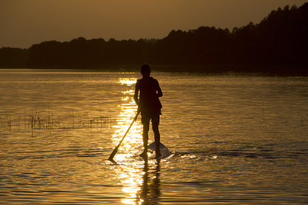 Silhouette boy on sup-board stand up paddle board Stock Photo