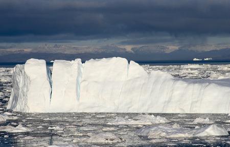 polar environment: Greenland glacier glaciers ocean dark blue sky mountains