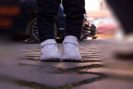 kid white sports shoes pads pavement blur jeans little legs boy standing
