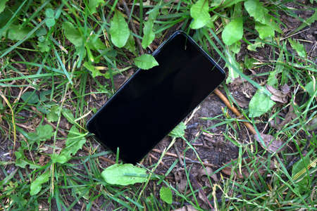 lost black smartphone cellphone grass meadow summer Stock Photo