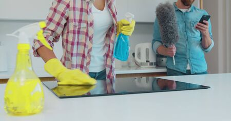 Cleaning cooktop cooking panel in kitchen with fat remover spray and a duster by a woman in yellow rubber gloves