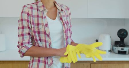 Determined wife ready to start cleaning the household, puts on yellow gloves