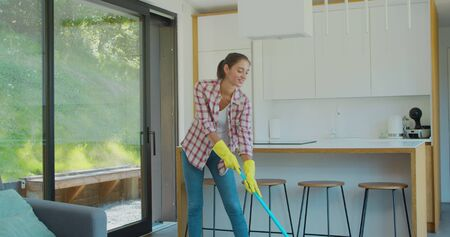Attractive girl is mopping floor at home and having fun. Women, joy and houses concept.