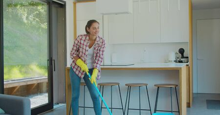 Attractive girl is mopping floor at home and having fun. Women, joy and houses concept. Фото со стока - 130100695