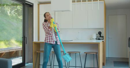 Beautiful young woman in protective gloves is singing using a mop and dancing while cleaning her house in living room during end of year clean. Фото со стока - 130100707