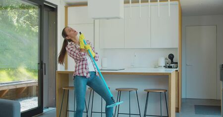 Beautiful young woman in protective gloves is singing using a mop and dancing while cleaning her house in living room during end of year clean. Фото со стока - 130100755