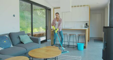 Attractive girl is listening to music and dancing wih mop during domestic work, she is mopping floor at home and having fun. Women, joy and houses concept. Фото со стока - 130100749