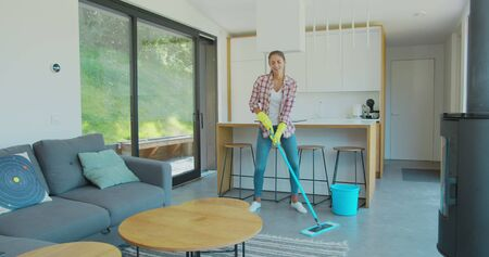 Attractive girl is listening to music and dancing wih mop during domestic work, she is mopping floor at home and having fun. Women, joy and houses concept. Фото со стока - 130100759