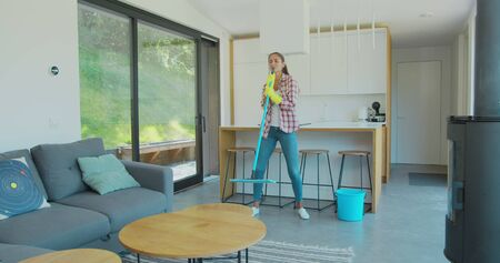Attractive girl is listening to music and dancing wih mop during domestic work, she is mopping floor at home and having fun. Women, joy and houses concept. Фото со стока - 130100773