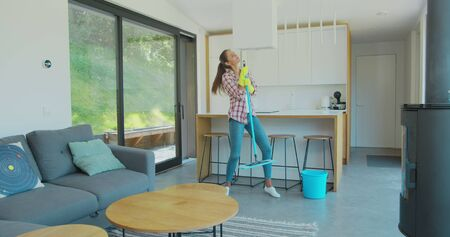 Attractive girl is listening to music and dancing wih mop during domestic work, she is mopping floor at home and having fun. Women, joy and houses concept.