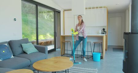Beautiful young woman in protective gloves is singing using a mop and dancing while cleaning her house in living room during end of year clean. Фото со стока - 130100782