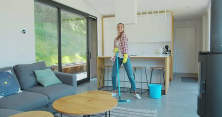 Beautiful young woman in protective gloves is singing using a mop and dancing while cleaning her house in living room during end of year clean. Фото со стока - 130102660