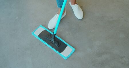 Cropped image of beautiful young woman in protective gloves using a flat wet-mop while cleaning floor in the house Фото со стока - 130102819