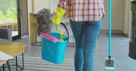 Cleaning concept. Woman with floor mop and bucket with washing fluids, back view Фото со стока - 130102854