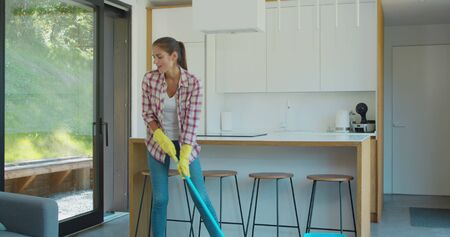 Beautiful young woman in protective gloves is singing using a mop and dancing while cleaning her house in living room during end of year clean.