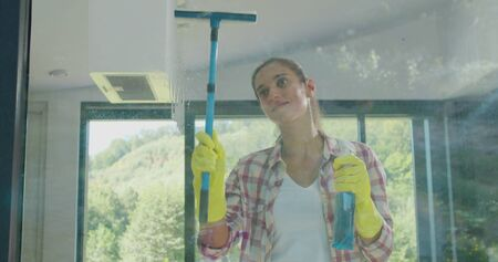 Girl removing cleaning solution from glass with special tool, cleaning service. Фото со стока