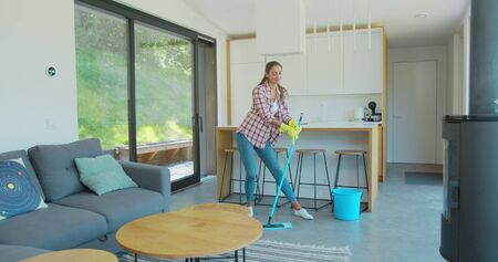 Beautiful young woman in protective gloves is singing using a mop and dancing while cleaning her house in living room during end of year clean. Фото со стока - 130104667