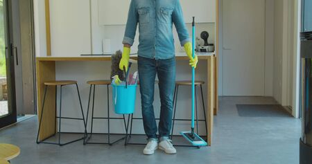 Man holding mop and plastic bucket with brushes, gloves and detergents in the kitchen.