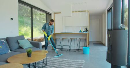 Man is mopping floor at home and having fun. Man, joy and houses concept. Фото со стока