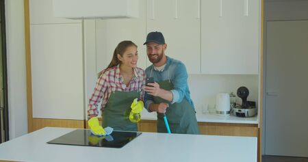Man and woman as a professional cleaners in uniiform having fun during the work on the kitchen